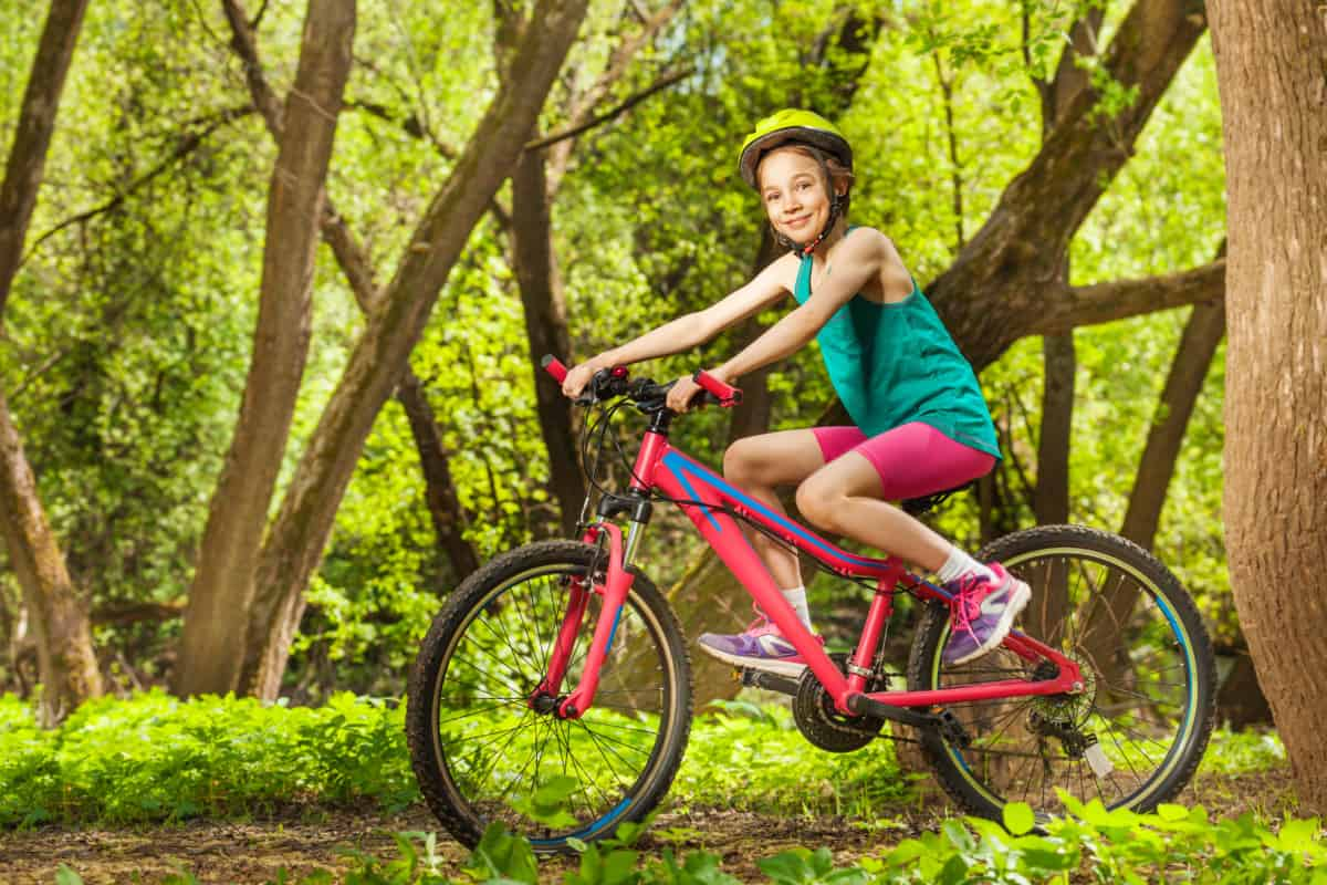 Smiling young girl cycling through spring woodland